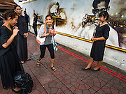 29 OCTOBER 2016 - BANGKOK, THAILAND: A woman walks past other women photographing themselves in front of a mural of the late Bhumibol Adulyadej, the King of Thailand. Saturday was the first day Thais could pay homage to the funeral urn of the late Bhumibol Adulyadej, King of Thailand, at Dusit Maha Prasart Throne Hall in the Grand Palace. The Palace said 10,000 people per day would be issued free tickerts to enter the Throne Hall but by late Saturday morning more than 100,000 people were in line and the palace scrapped plans to require mourners to get the free tickets. Traditionally, Thai Kings lay in state in their urns, but King Bhumibol Adulyadej is breaking with tradition. His urn reportedly contains some of his hair, but the King is in a coffin,  not in the urn. The laying in state will continue until at least January 2017 but may be extended.       PHOTO BY JACK KURTZ
