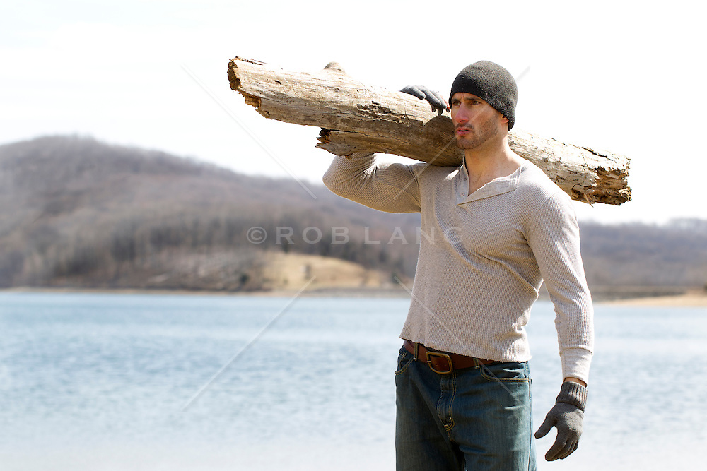 rugged handsome man with a large log on his shoulder