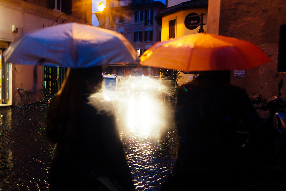 Twenty somethings walk to dinner in the rain in Rome, Italy