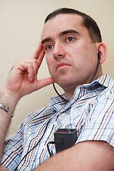 Man with hearing impairment studying with audio machine.