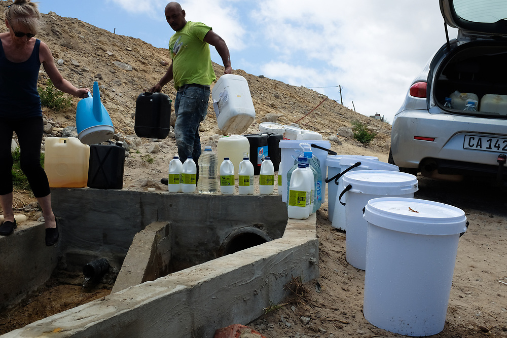 People collect water at Dido Valley spring. Water flows from a spring in the ground near a new construction site.