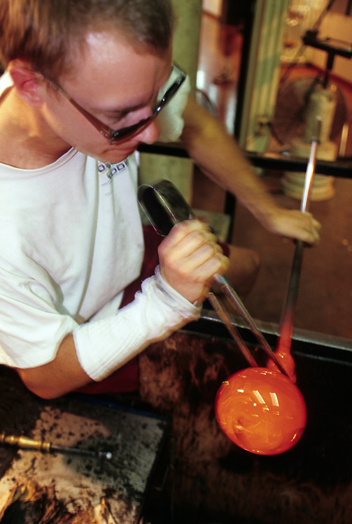 United States, Washington State, Seattle. Glassblower with red-hot vessel