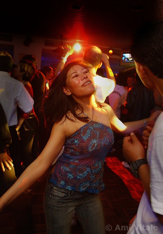 Nepalese dance in a nightclub in Katmandu, seemingly unaware of the brutal conflict that lies just outside the city in Nepal March 5, 2005. (Ami Vitale)