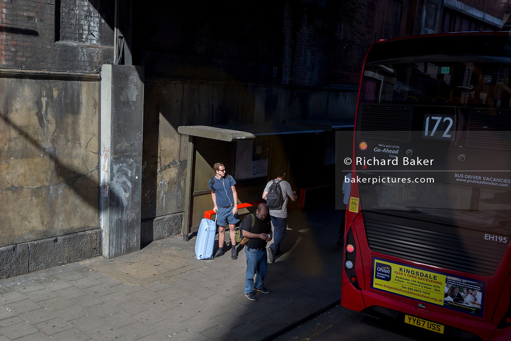 A young traveller waits for a bus at Waterloo station in the capital, 22nd August 2019, in London, England.