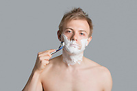 Portrait of tired man shaving over colored background