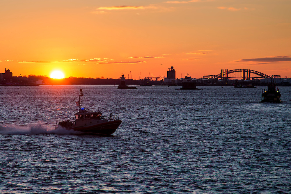 A United States Coast Guard (USCG) boat sails across the Upper Bay, New York City, New York, United States of America,  at sun set other boats also travel across the water and the Bayonne Bridge and building of New Jersey are silhouetted in the background. (photo by Andrew Aitchison / In pictures via Getty Images)