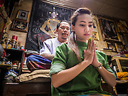 "25 MAY 2015 - BANGKOK, THAILAND:  AUEN, a Thai woman who sells cosmetics, prays while she gets a Sak Yant tattoo from Ajarn Neng Onnut in his tattoo parlor in Bangkok. Sak Yant (Thai for ""tattoos of mystical drawings"" sak=tattoo, yantra=mystical drawing) tattoos are popular throughout Thailand, Cambodia, Laos and Myanmar. The tattoos are believed to impart magical powers to the people who have them. People get the tattoos to address specific needs. For example, a business person would get a tattoo to make his business successful, and a soldier would get a tattoo to help him in battle. The tattoos are blessed by monks or people who have magical powers. Ajarn Neng, a revered tattoo master in Bangkok, uses stainless steel needles to tattoo, other tattoo masters use bamboo needles. The tattoos are growing in popularity with tourists, but Thai religious leaders try to discourage tattoo masters from giving tourists tattoos for ornamental reasons.       PHOTO BY JACK KURTZ"