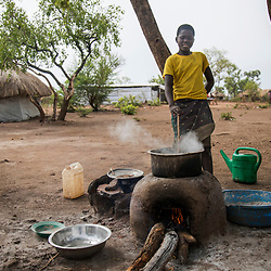Twelve-year-old Anna cooks maize at Bidi Bidi Refugee Camp in northern Uganda. Her parents were killed in South Sudan and she has lived here with her grandmother since August last year.