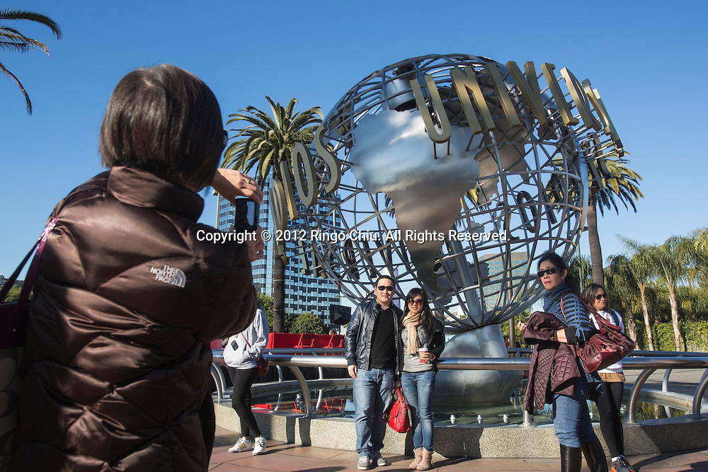 Chinese tourists take pictures at the Globe Fountain in Universal Studios Hollywood. .(Photo by Ringo Chiu/PHOTOFORMULA.com).