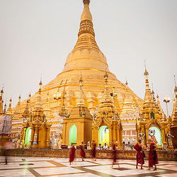 Group of monks in front of the Shwedagon pagoda at dusk, Yangon, Myanmar, Asia