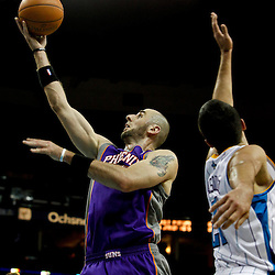 February 2, 2012; New Orleans, LA, USA; Phoenix Suns center Marcin Gortat (4) shoots over New Orleans Hornets power forward Gustavo Ayon (15) during the second half of a game at the New Orleans Arena. The Suns defeated the Hornets 120-103.  Mandatory Credit: Derick E. Hingle-US PRESSWIRE