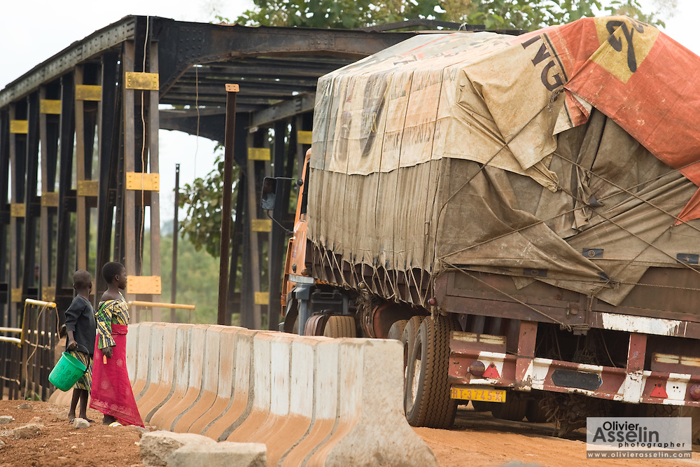 Girls watch as vehicles cross a bridge intended for trains opened to road traffic to replace a  bridge that collapsed due to heavy rains near Notse, Togo on Friday September 11, 2009.