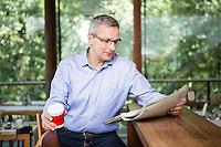Österreich, Portrait Mann / Geschäftsmann, an Theke eines Restaurants, Zeitung lesend, Kaffeepause, Casual Look, Pause, Entspannung