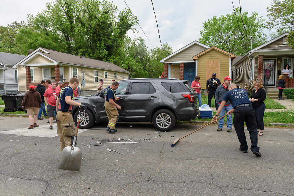 Louisville Metro Police and Fire departments respond to an auto accident on the street where a group of Owens-Corning employees work at a Habitat for Humanity build Friday, April 21, 2017, at 2320 St. Louis Ave. in Louisville, Ky. The driver of the Impala was injured but her daughter was safe in a car seat in the rear of the vehicle. The Honda struck by the Impala was driven by a Habitat for Humanity volunteer arriving onsite to work. Both were taken by ambulance to the hospital, and a vehicle owned by an Owens Corning employee was also injured in the crash. (Photo by Brian Bohannon)