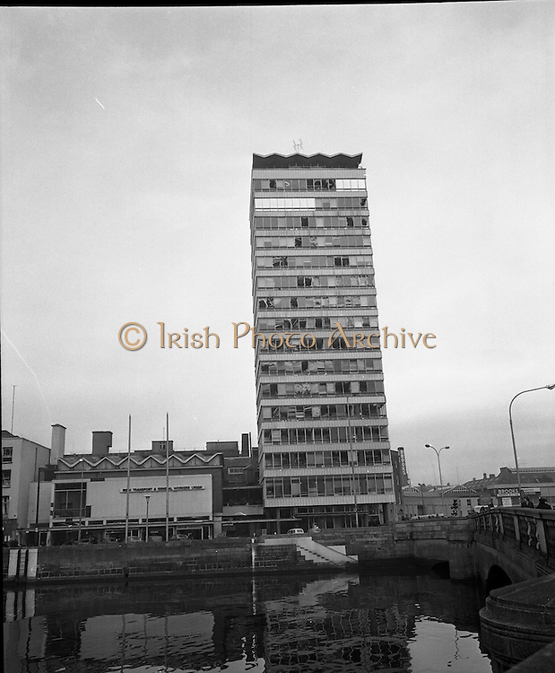 Car Bomb Damage in Dublin (E10)..1972.02.12.1972..12.02.1972..2nd December 1972..On the morning of 2nd December '72 two car bombs exploded in Dublin City. At Sackville Place two busmen were killed as they waited in their car to resume work. The busmen were named as George Bradshaw (30) and Thomas Duffy (23). The bomb was thought to be planted by a Northern Ireland subversive group who hoped to influence legislation going through Dail Eireann in relation to the I.R.A...Picture taken in the cold light of day shows the blast damage to Liberty Hall on Eden Quay. The shock wave was powerful enough to take out windows on the top floor of the building.