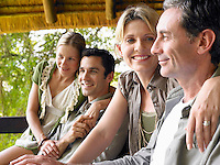 Two couples sitting on terrace smiling