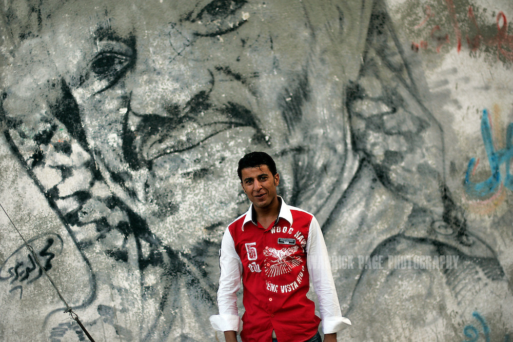 GAZA CITY, GAZA STRIP - AUGUST 20: Mohammed Al-Dira stands in front of one of his portraits of Yasser Arafat , August 20, 2009, Gaza City, Gaza Strip. When Hamas took over Gaza it forbid artists from painting or writing any pro-Fatah graffiti. Since the two factions became bitter rivals, there is little room for  political dissent within either territory. (Photo by Warrick Page)