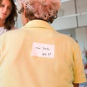 Nederland Rotterdam  31-08-2009 20090831 Foto: David Rozing .Serie over zorgsector, Ikazia Ziekenhuis Rotterdam, afdeling neurologie. Zuster noteert medische gegevens van een oude demente vrouw, zij loopt telkens weg van de afdeling. Op haar rug is een sticker met daarop haar naam en afdeling geplakt voor het geval ze zoek raakt. Nurse escorts old demented lady back to her room, from which she keeps walking away from. They put a sticker on her back with her name and room number on it in case she takes off again and is missing. ..Foto: David Rozing   ..Holland, The Netherlands, dutch, Pays Bas, Europe, ronde doen, routine verpleegkundigen, op zaal liggen, interactie patient verpleging, praatje maken met, tijd hebben voor, aandacht hebben voor geven, luisterend oor hebben voor ,onherkenbaar, onherkenbare, unrecognisable, nursing,  ,ziektekosten,zorgverlener, zorgverleners,zorgverlening, amnesie, geheugenverlies, alzheimer, verward zijn, verwardheid, desorientatie, orientatievermogen, aftakelen, aftakeling, de weg kwijt zijn, verstandelijke vermogens kwijtraken, losing the mind, dementia, disorientated, disorientation, dementeren,,oud ,ouderen, bejaard, bejaarde, bejaarden, op leeftijd zijn, oude van dagen, ouderenzorg,oudere bejaardenzorg, ouderdom,verpleegster, verpleegsters, verpleger, verplegers, verplegend, status...Foto: David Rozing