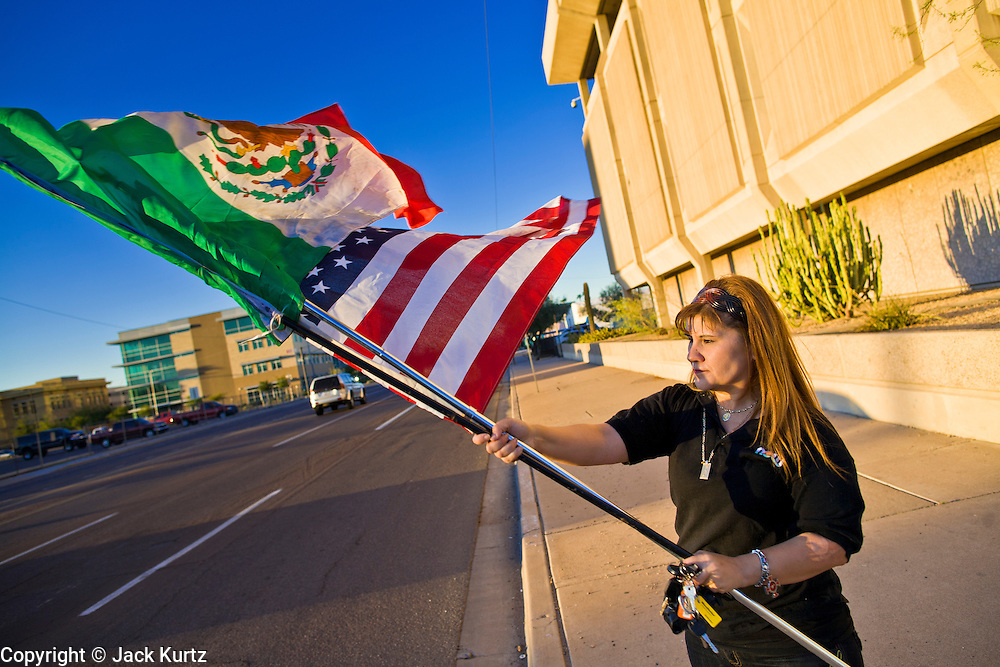 11 OCTOBER 2010 - PHOENIX, AZ:  HILDA CANALES, from Phoenix, AZ, waves the American and Mexican flags in front of the Phoenix police headquarters Monday night. About 300 people gathered at the Phoenix Police Department headquarters building Monday night to protest the shooting of Daniel Rodriguez and his dog. The officers responded to a 911 call made by Rodriguez' mother. A scuffle ensued when they arrived and Phoenix police officer Richard Chrisman shot Rodriguez, who was unarmed, and his dog. Chrisman then allegedly filed a false report about the event. He has been arrested on felony assault charges. The event has angered some in the Latino community and they have held a series of protests at the police headquarters. They want Chrisman charged with murder.    Photo by Jack Kurtz