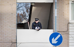 © Licensed to London News Pictures. 07/03/2019. London, UK. A police officer watches from a block of flats next to the crime scene in North Birkbeck Road in Leyton in east London where a murder investigation has been launched after a man in his twenties was stabbed on Wednesday. Photo credit: Peter Macdiarmid/LNP