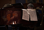 Local member of the Provincial Legislature Nick Simons is reflected in the grand piano while rehearsing a show with pianist Helena Sandler at the 100-year-old Patricia Theatre in Powell River, BC. (2013)
