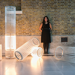 London, UK - 15 September 2014: A member of the staff stands next to 'Column (Assemblages) V, 2010' by Cerith Wyn Evans during the press preview of his new solo exhibition at Serpentine Sackler Gallery.