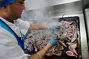"A chef working for the world's largest independent provider of airline catering and provisioning services, Gate Gourmet, fries Welsh Lamb cutlets in the company's factory on the southern perimeter road at Heathrow Airport, West London. Gate Gourmet serve more than 200 million meals on 2 million airline flights a year to their 250-plus airline customers at more than 100 airport locations around the globe. Apart from creating the bespoke meals for an airline's culture and ethnic demands, that pack the pre-flight carts, deliver and load into the aircraft galleys and afterwards, they dispose of the waste and strip, wash and sterilize the equipment. From writer Alain de Botton's book project ""A Week at the Airport: A Heathrow Diary"" (2009). ."