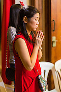 24 DECEMBER 2013 - BANGKOK, THAILAND: A woman prays in the breezeway outside the church during Christmas services at Holy Redeemer Church in Bangkok. Thailand is predominantly Buddhist but Christmas is widely celebrated throughout the country. Buddhists mark the day with secular gift giving but there are about 300,000 Catholics in Thailand who celebrate religious Christmas. Catholics first came to Thailand (then Siam) in 1567 as chaplain for Portuguese mercenaries in the employ of the Siamese monarchy. There has been a continuous Catholic presence in Thailand since then.   PHOTO BY JACK KURTZ