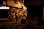 Policemen move forward during an incursion by security forces into 'Rocinha', one of Brazil's biggest slums controlled by drug traffickers, on November 13, 2011, Rio de Janeiro, Brazil. Photo by Mauricio Lima for The New York Times