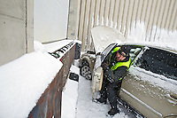 Derek Miller, with Schaffer's Towing, exits a vehicle after preparing it for towing Wednesday at the Coeur d'Alene Press loading dock where it crashed into the building. The driver, who was driving without a license, lost control of the vehicle in the snow on Second Street after turning off of Coeur d'Alene Avenue. There were no injuries reported in the accident.