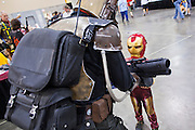 27 MAY 2011 - PHOENIX, AZ: A child dressed as Iron Man checks out a Star Wars character's weapon at Comicon in Phoenix Friday. Phoenix Comicon opened Thursday and featured a Zombie Walk through downtown Phoenix Friday night. Hundreds of people participated in the Zombie Walk, both as Zombies and as Zombie hunters. This year's Comicon includes appearances by Leonard Nimoy (Star Trek), Adam Baldwin (Firefly and Chuck), Stan Lee (Marvel Comics), Nicholas Brendon (Buffy the Vampire Slayer) and others. Activities include costuming workshops, role playing games and a Geek Prom.     Photo by Jack Kurtz