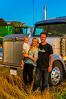 A farm family during the wheat harvest standing in front of a tractor trailer and combine harvester, Schields & Sons Farming, Goodland, Kansas USA.