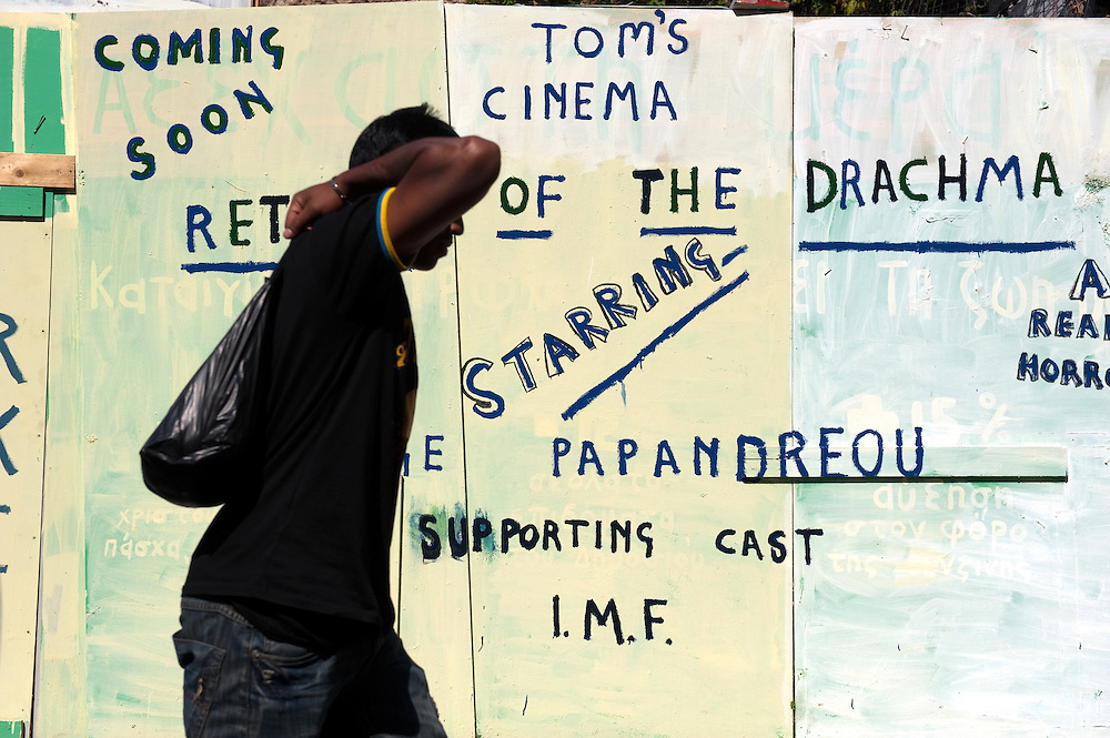 Man passing by graffiti in Plaka, Athens Greece. Return of the Drachma, starring George Papandreou, supporting cast IMF