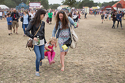 © Licensed to London News Pictures . 20/07/2013 . Suffolk , UK . Two women carry a young girl above the ground . The Latitude music and culture festival in Henham Park , Southwold . Photo credit : Joel Goodman/LNP