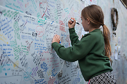© Licensed to London News Pictures. 16/06/2017. London, UK. A young girl signs a memorial wall  for the victims of the Grenfell tower block fire in west London. The blaze engulfed the 27-storey building killing 12 - with 34 people still in hospital, 18 of whom are in critical condition. The fire brigade say that they don't expect to find anyone else alive. Photo credit: Guilhem Baker/LNP