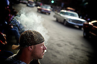A spectator enjoys a cigar as he watches hundreds of classic cars slowly roll along the downtown route of the Car d'Lane cruise Friday, June 17, 2011 in Coeur d'Alene, Idaho