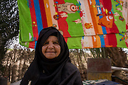 Portrait of an 88 year-old local woman with a background of drying towels in Bairat, a village on the West Bank of Luxor, Nile Valley, Egypt.