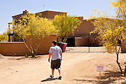 "22 MAY 2011 - SCOTTSDALE, AZ:  A man walks back to the house after putting up a ""No Trespassing"" sign in front of a home reportedly owned by Sarah Palin in Scottsdale, AZ. According to the Arizona Republic, Sarah Palin and her husband Todd Palin, bought the 8,000 square foot home for $1.695 million cash. The newspaper said the Palin's name does not appear on the paperwork and the home was bought by Safari Investments LLC out of Delaware. The paper said the deal ""appears designed to cloak the identity of a high-profile buyer."" The home has six bedrooms, five bathrooms, a six car garage, swimming pool, spa, home theater, wine cellar and children's ""jungle gym"" in the backyard. The home is surrounded by a tall wall with an electronic gate. Phoenix TV stations have reported that a black SUV with Alaska license plates has been seen entering and leaving the compound. People in the house have refused to comment on who owns the home. Neither Palin nor her husband have been seen at the home since news of the sale broke Saturday, May 21.   Photo by Jack Kurtz"