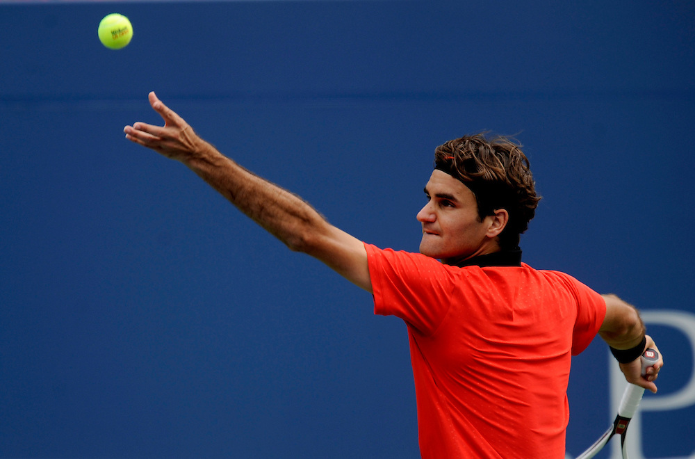 NEW YORK - AUGUST 31: Roger Federer tosses a ball to serve against Devin Britton during day one of the 2009 U.S. Open at the USTA Billie Jean King National Tennis Center on August 31, 2009 in Flushing neighborhood of the Queens borough of New York City. (Photo by Rob Tringali) *** Local Caption *** Roger Federer