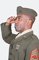 Male US soldier saluting over gray background