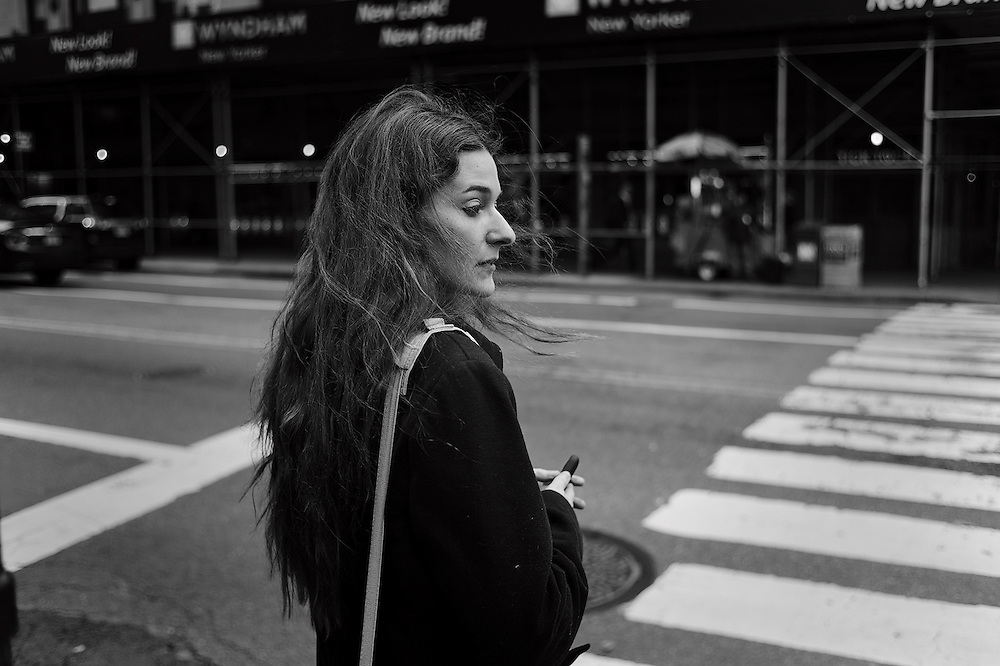Woman waiting to cross street, New York, NY, US