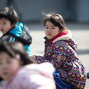 OGA, JAPAN - MARCH 17: Students at the Hokuyou Elementary School is seen sitting on the ground during a missile evacuation drill on Friday, March 17, 2017, in Kitaura, Oga, Akita Prefecture, Japan. During the drill, around 50 kids were instructed to walk slowly inside of a school gym, as if a missile had hit the the ground nearby. After a loud siren, people are instructed through a loud speaker to move to safer ground in the school. People participated in the first missile evacuation drill organized by the Akita prefectural office and Oga city to prepare people in the event of a North Korean Missile strike on Japan. Recently, Three of four missiles fired by North Korea may have fallen into Japan's Exclusive Economic Zone and the Japanese government has lodged a strong protest against North Korea. (Photo: Richard Atrero de Guzman/ANADOLU Agency)