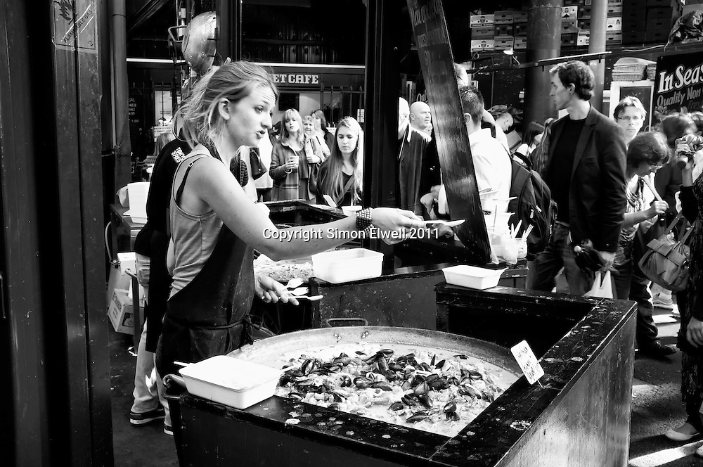 Woman sells food in Borough Market, London