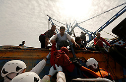 A rescued migrant climbs down from a Tunisian fishing vessel onto a rigid hulled inflatable boat (RHIB) of the Malta-based NGO Migrant Offshore Aid Station (MOAS) to be taken to the Dutch rescue ship Sea-Eye, after some migrants on a rubber dinghy drowned in the central Mediterranean in international waters off the coast of Libya, April 16, 2017. REUTERS/Darrin Zammit Lupi