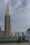 A mother wheels a pushchair in front of Docomo Tower in Shinjuku, Tokyo, Japan Friday June 9th 2017