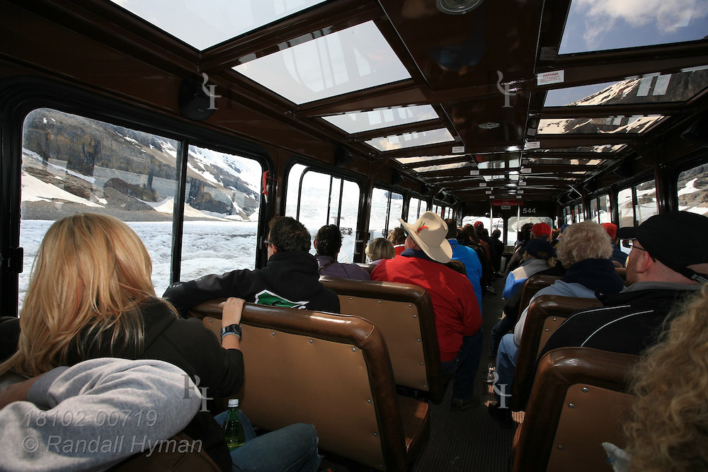Tourists ride in all-terrain bus to experience traveling and walking on the Columbia Icefield; Jasper National Park, Alberta, Canada.
