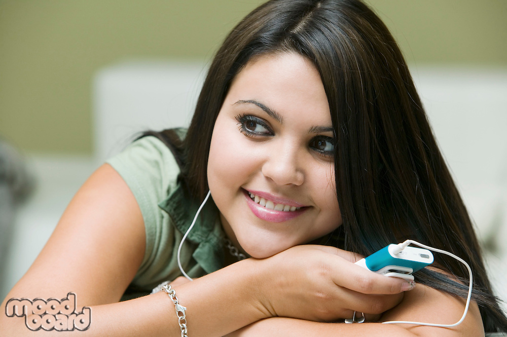 Young woman lying on sofa listening to MP3 player close up