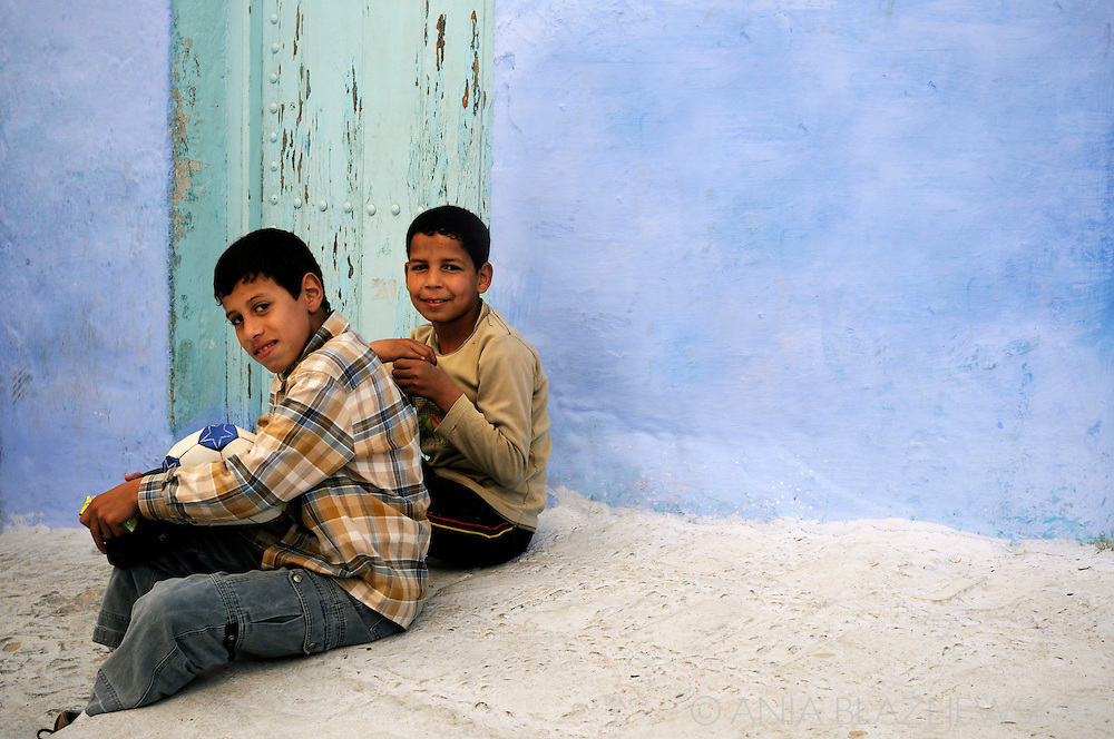 Morocco, Chefchaouen. Boys sitting on the stairs in one of the streets.