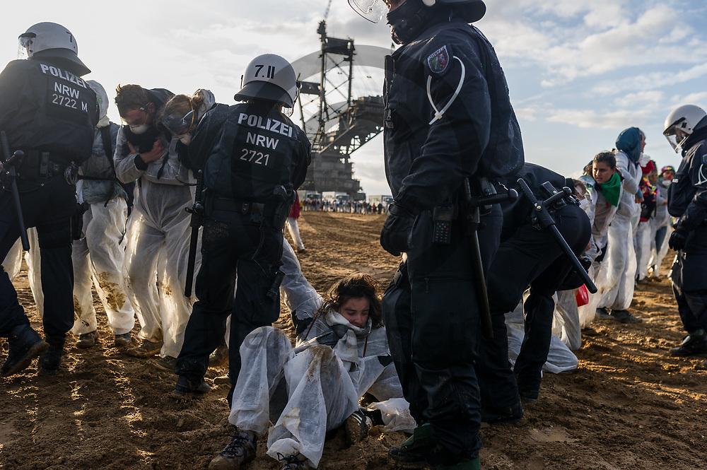 Deutschland, Elsdorf - 05.11.2017<br /> <br /> Polizisten dr&uuml;cken Aktivisten zur&uuml;ck. Circa 2500 Aktivisten drangen in die Grube des Braunkohle Tagebau Hambach ein um mit der Aktion f&uuml;r einen sofortigen Kohleausstieg zu protestieren. Die Aktion fand im Rahmen von Protesten im Vorfeld der UN-Klimakonferenz in Bonn statt.<br /> <br /> Germany, Elsdorf - 05.11.2017<br /> <br /> Policemen push back activists. Approximately 2500 activists invaded the pit of the lignite opencast mine Hambach to protest for an immediate coal exit. The action took place during protests prior to to the UN Climate Change Conference in Bonn.<br /> <br />  Foto: Markus Heine<br /> <br /> ------------------------------<br /> <br /> Ver&ouml;ffentlichung nur mit Fotografennennung, sowie gegen Honorar und Belegexemplar.<br /> <br /> Bankverbindung:<br /> IBAN: DE65660908000004437497<br /> BIC CODE: GENODE61BBB<br /> Badische Beamten Bank Karlsruhe<br /> <br /> USt-IdNr: DE291853306<br /> <br /> Please note:<br /> All rights reserved! Don't publish without copyright!<br /> <br /> Stand: 11.2017<br /> <br /> ------------------------------