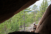 David Coffey scrambles into a cave to take shelter from an impending storm in the Lost Creek Wilderness, Colorado.
